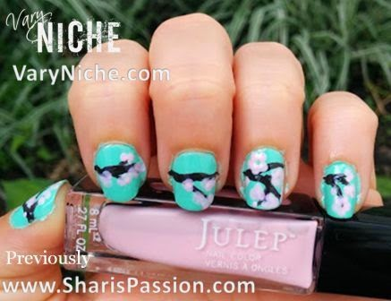 Fingernails with pale pink flowers dotted over a dark brown branch running across nails with a teal background.