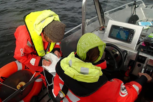 Kaksi kartoittajaa töissä. Toinen ajaa venettä ja toinen kirjaa havaintoja ylös.