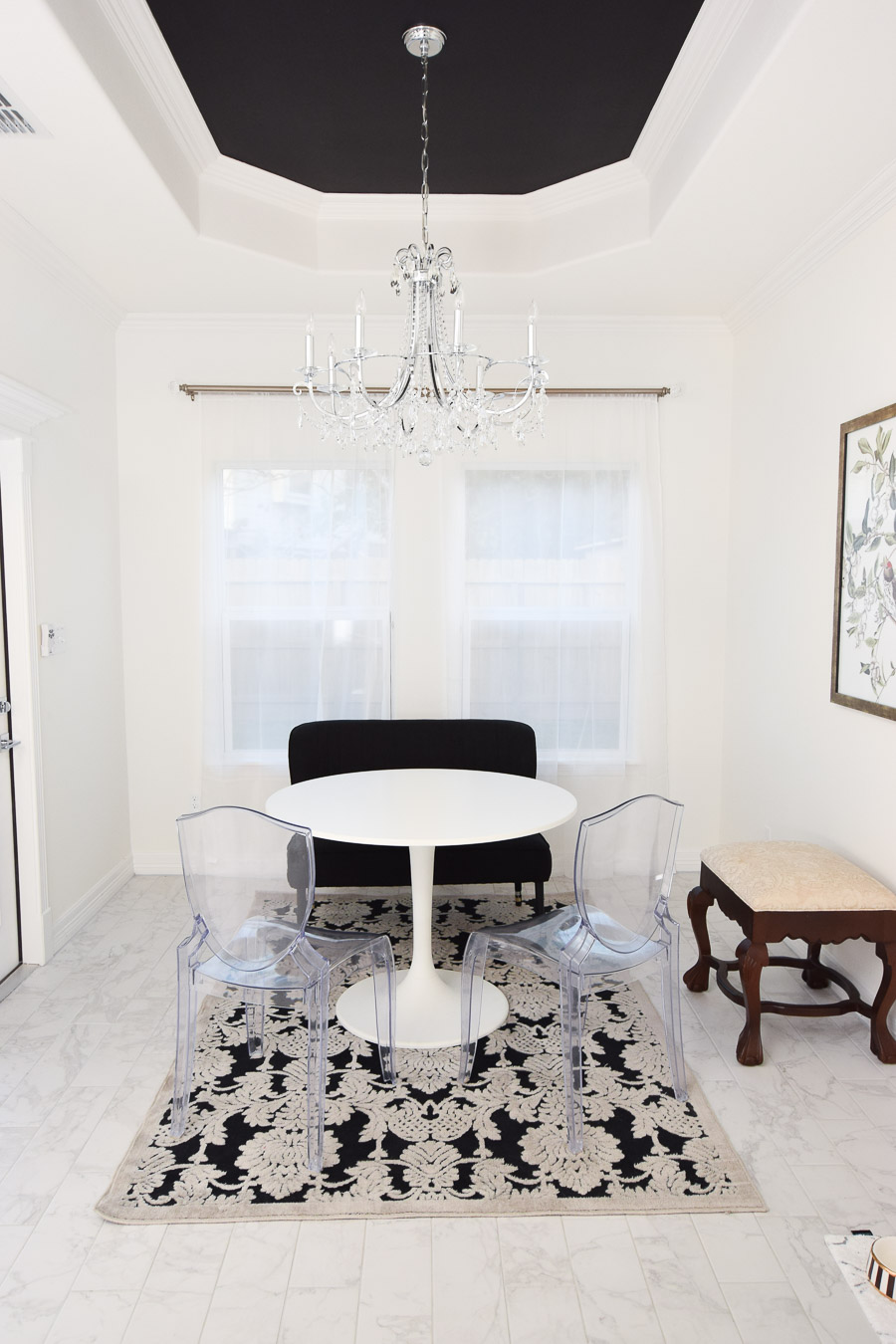 IKEA docksta table paired with ghost chairs and a small loveseat bench in a dining space.