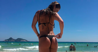 Aos 40 anos, Dany Bananinha exibe boa forma de biquíni branco na praia
