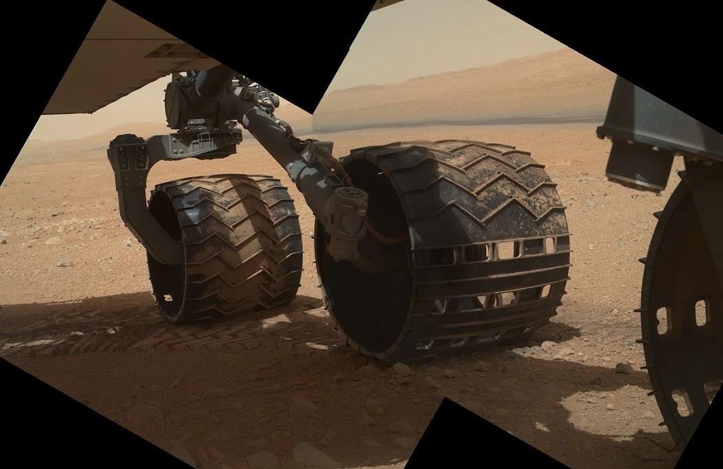 Vào ngày 9 tháng 9 năm 2012 khi con tàu chuẩn bị cho một ngày làm việc mới, nó đã chụp lại hình ảnh cận cảnh vào hai bánh xe trái của mình. Trong hình ở phía xa, là đoạn dốc thoải của Núi Sharp. Hình ảnh: JPL-Caltech/MSSS/NASA.