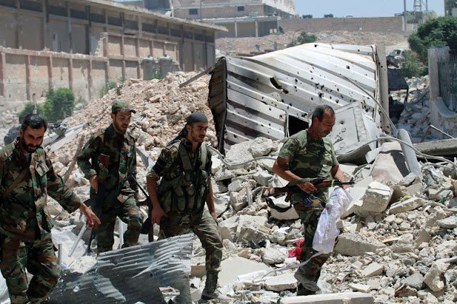 Forces loyal to Syria's President Bashar al-Assad walk with their weapons past rubble after they advanced on the southern side of the Castello road in Aleppo, Syria