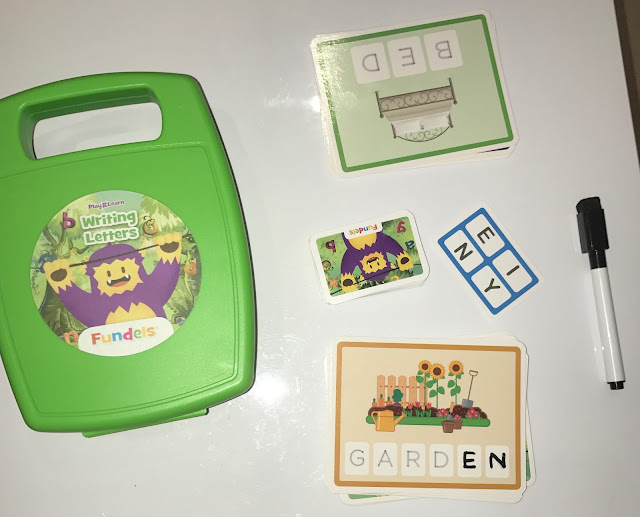 The green case of the writing letters game next to cards saying Garden and Bed, a dry wipe pen and a letters card with the letters E, I, N and Y