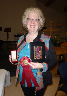 woman holding a completed embroidery project of a red and purple bird, a red prize ribbon and a box with a pendant in it