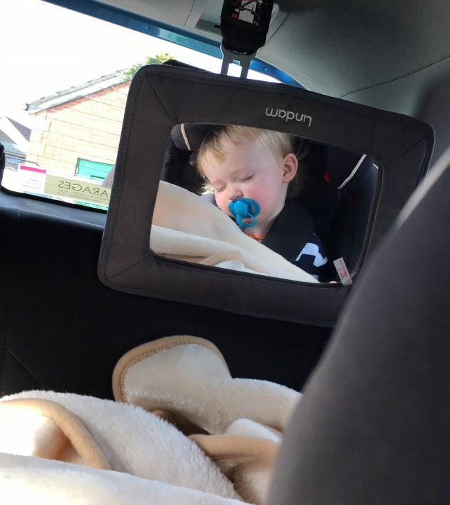 reflection in mirror of toddler asleep in car seat with dummy