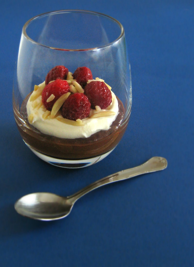 mousse em copo decorada com chantilly, framboesas e amêndoas palitadas / mousse on a glass topped with whipped cream, raspberries and sliced almods