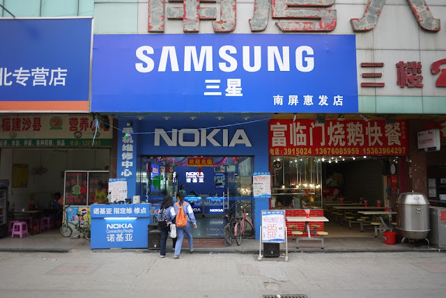 store with many Nokia signs with a larger Samsung sign at the top