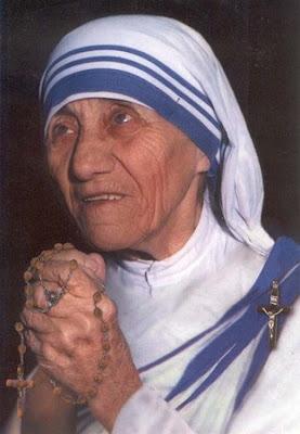 La Madre Teresa de Calcuta vestida con el habito de las Hermanas de Loreto y un rosario en sus manos.