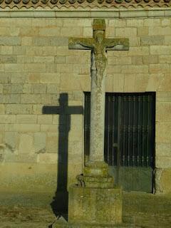 crucero y su sombra reflejada en la pared de la ermita.