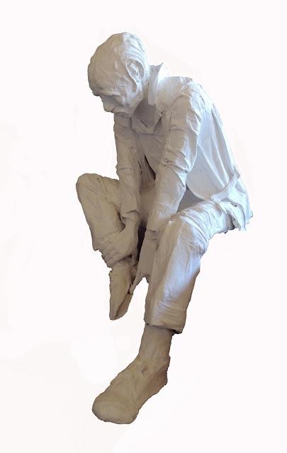 escultura al yeso de Francesc Anglès hombre sentando observando sus zapatos