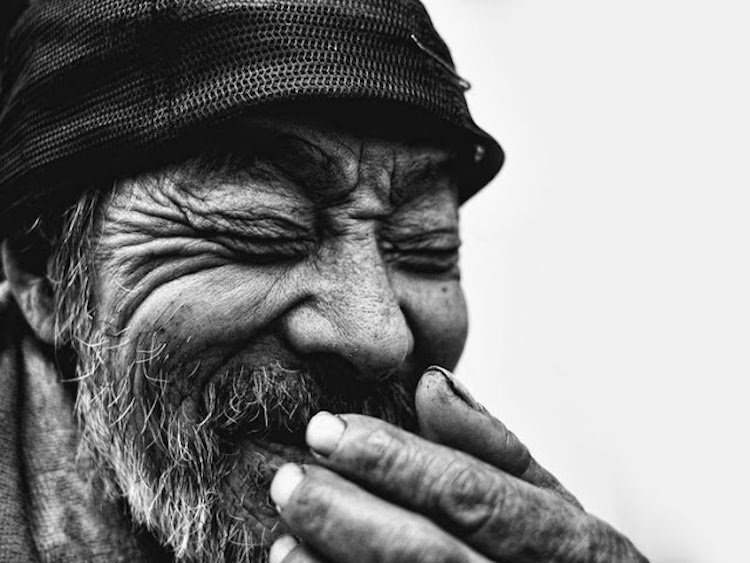Gorgeous black and white photo of an old man covering his mouth while laughing Best April Fool. MarchMatron.com