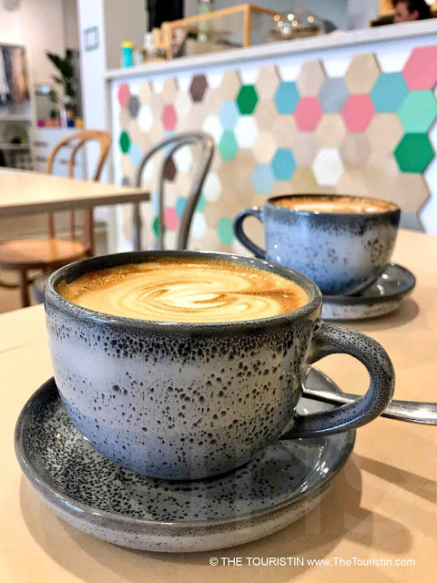 Two Flat White espresso drinks in dark grey cups on a light wooden table with a colourful counter in the background