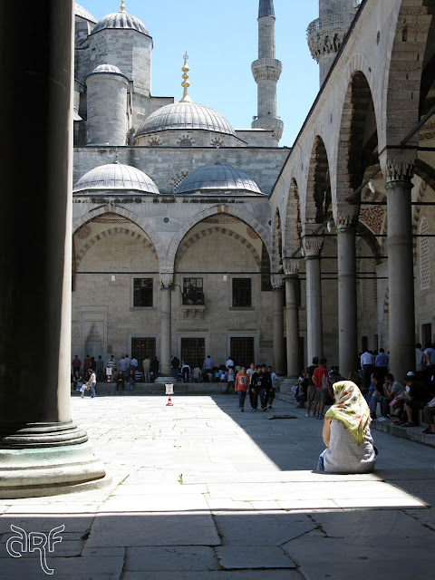 woman sitting in square of mosque, Istanbul