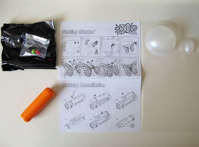 I DO 3D pens and pen tips in packets, an instruction sheets, plastic forms and a spotlight.