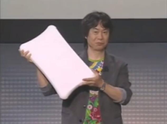 Shigeru Miyamoto holding up a Wii Balance Board E3 2007 Fit