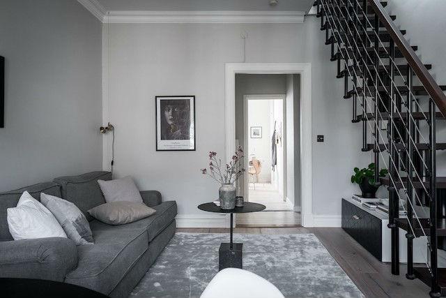 Salón decorado en tonos neutros con silla mariposa, escalera y suelo de madera natural