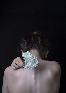a woman's bare back | white flowers in her hand
