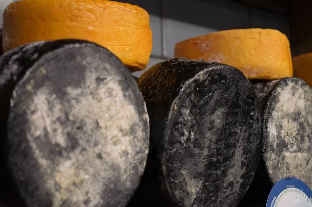 diferentes queijos expostos numa bancada do mercado central