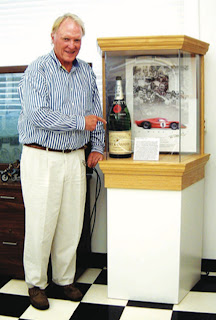 Dan Gurney with the original Moët bottle in the All American Racers' boardroom.  Photo Courtesy of All American Racers