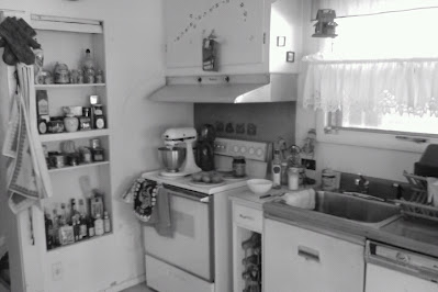 very old and cluttered kitchen in black and white