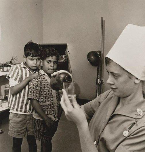 Vintage foto: dos niños miran con duda y sorpresa el trabajo de una enfermera que vierte la medicina en un vaso.