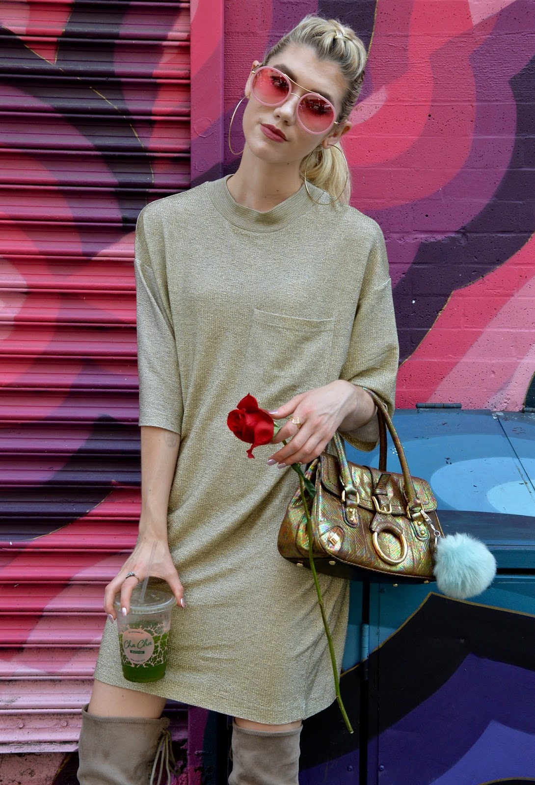 Giving sass in a gold tee shirt dress with a vintage purse and rose.