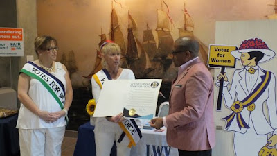Erie County government representative presents proclamation to two members of League of Women Voters