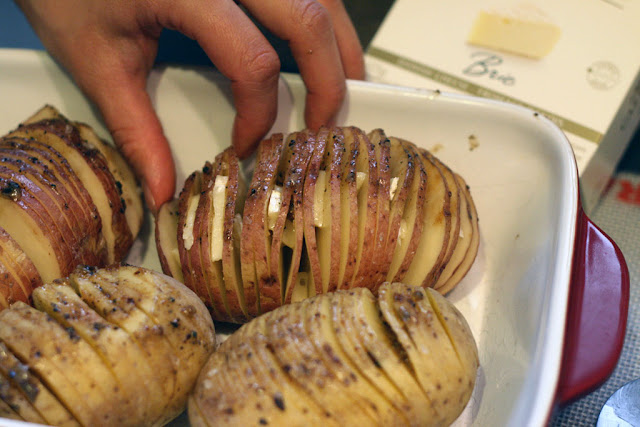 Picture from above of the hasselback potatoes being stuffed with brie cheese.