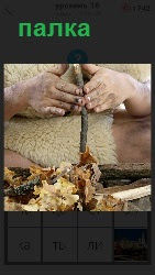 человек крутит палкой для добычи огня и стружка приготовлена