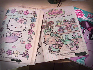 Two open Hello Kitty coloring books open with signitures blacked out.  An my little pony friendship is magic coloring book closed under the other two.