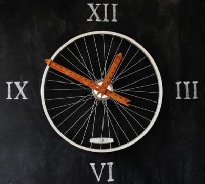Jam dinding terbuat dari roda sepeda sebagai bingkai dan penggaris kayu sebagai jarum jam
