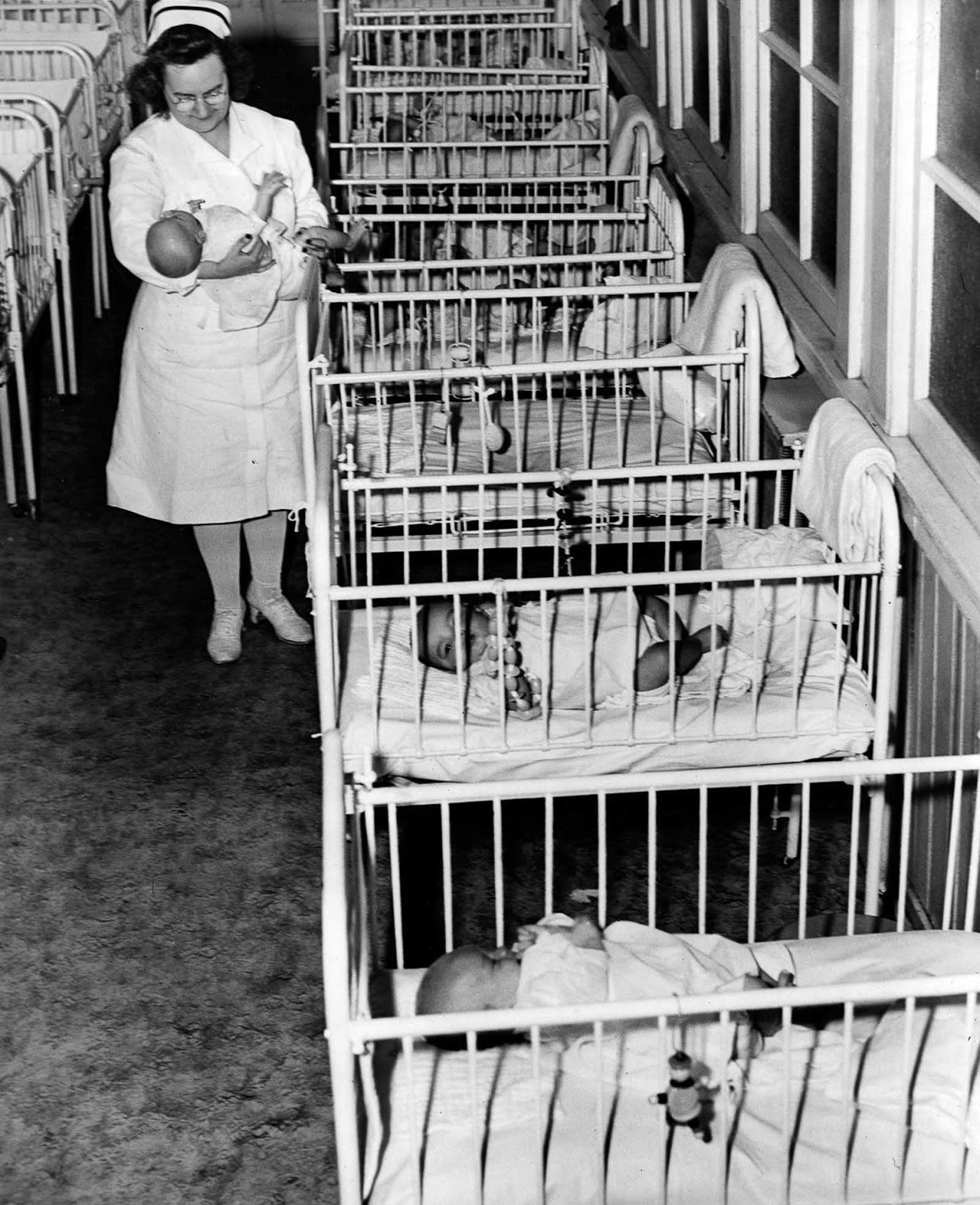 A nurse cares for one of many infants at St. Ann's Infant Asylum in Washington, D.C. 1946.