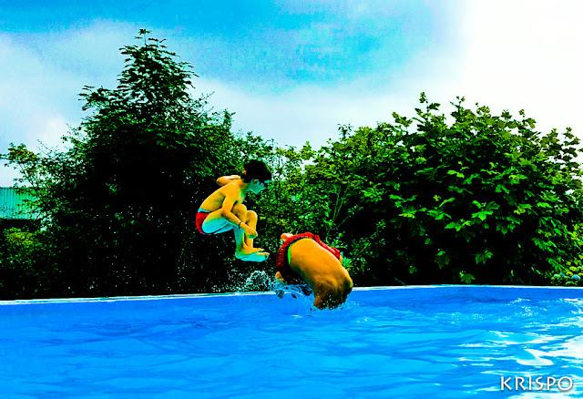 dos niños dandose un chapuzon en la piscina