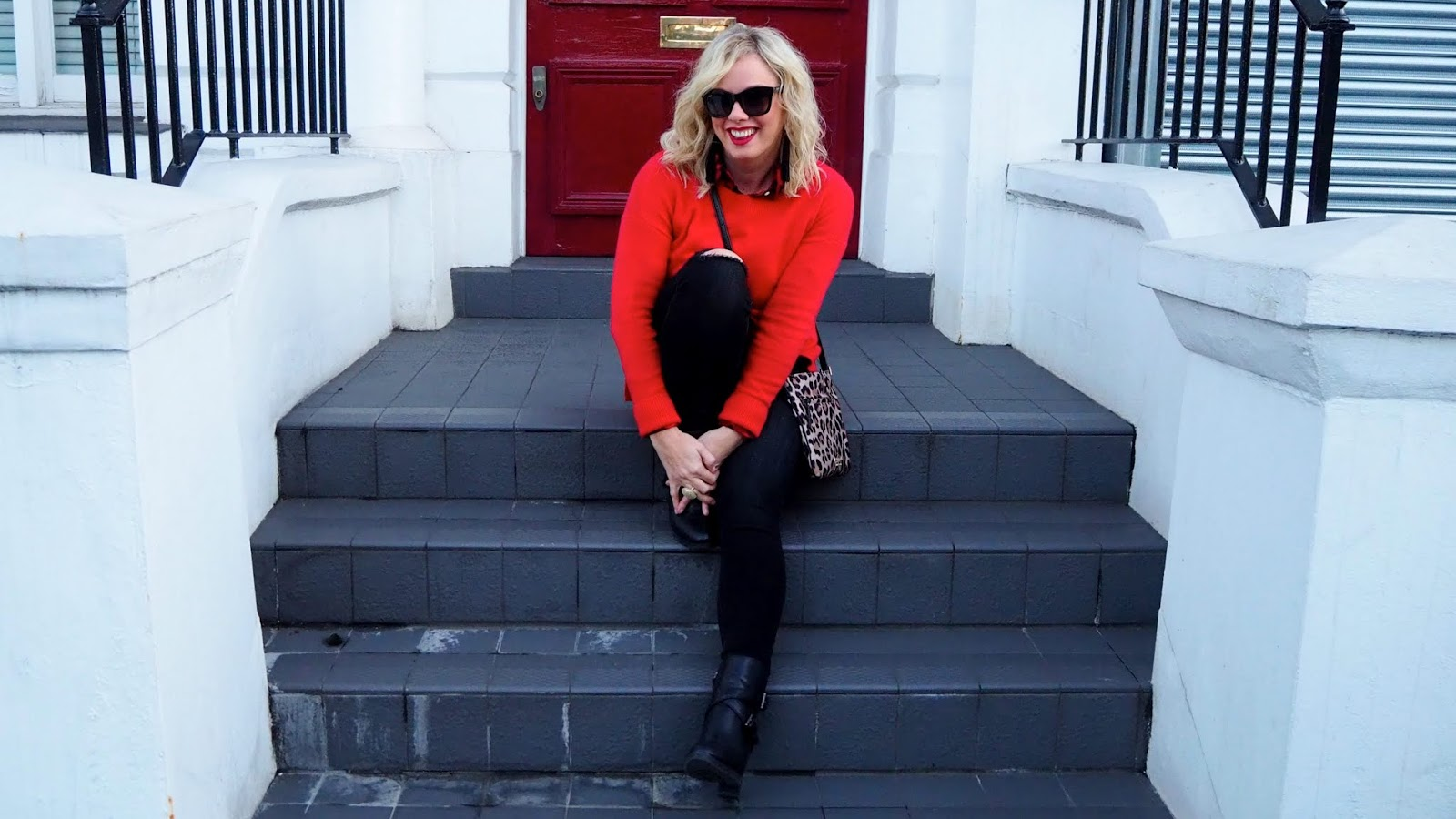 red sweater, leopard bag, black jeans on a blonde sitting on the steps in London