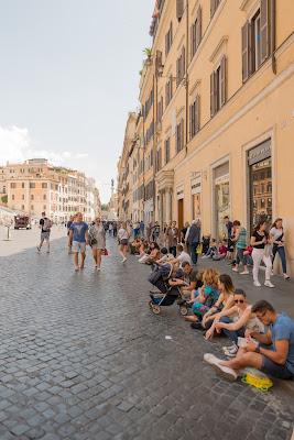 Tourists sitting on a Roman street