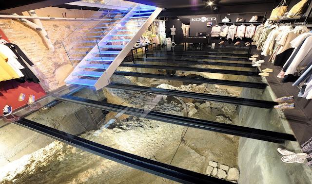vista de la tienda, con suelo de vidrio y vista a las ruinas romanas del subsuelo