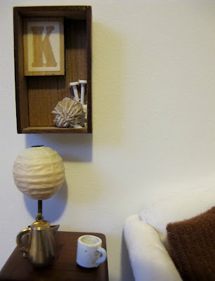 Modern dolls' house miniature scene of a side table with lamp, coffee pot and mug. On the wall above it is a box frame with the letter K, a ball of wool and two knitting needles.