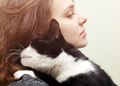 Woman cuddling black-and-white cat
