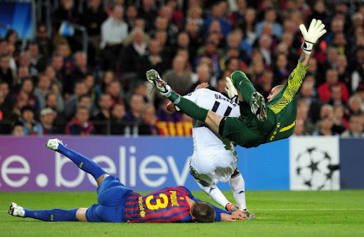 Gerard Piqué lies on the ground after getting knocked down by his own goalkeeper Víctor Valdés