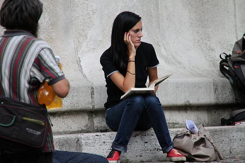 Jeune femme réfléchissant, un livre posé sur ses genoux.