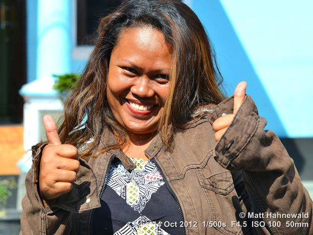 street portrait, Indonesia, Central Sulawesi, double thumbs-up sign, modern Indonesian woman, charming, outgoing, smiling, posing