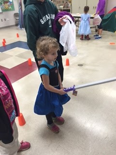 Young girl in princess dress holding a fake sword