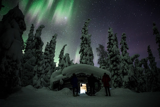 Pieni torppa lumisessa metsässä ja taivaalla revontulet