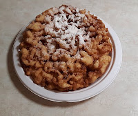 Small funnel cake on a cardboard plate.