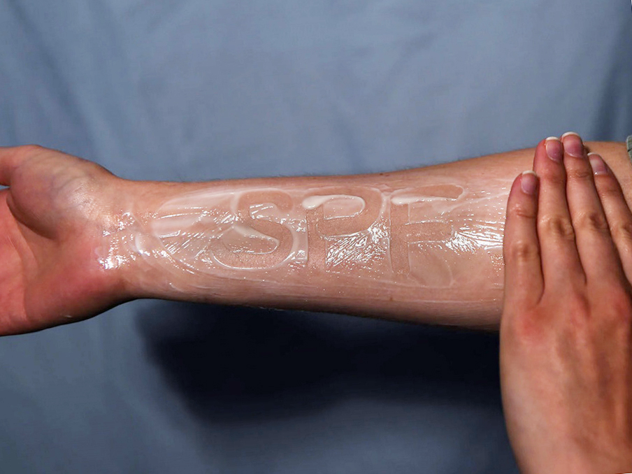 """A forearm covered in a thick layer of sunscreen with """"SPF"""" written in it"""