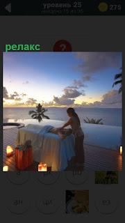 На берегу на закате на столе релакс делает массажистка