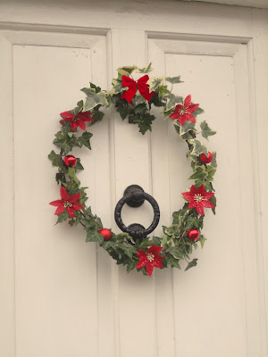 Ivy wreath on white front door, with red bow, baubles and poinsettia