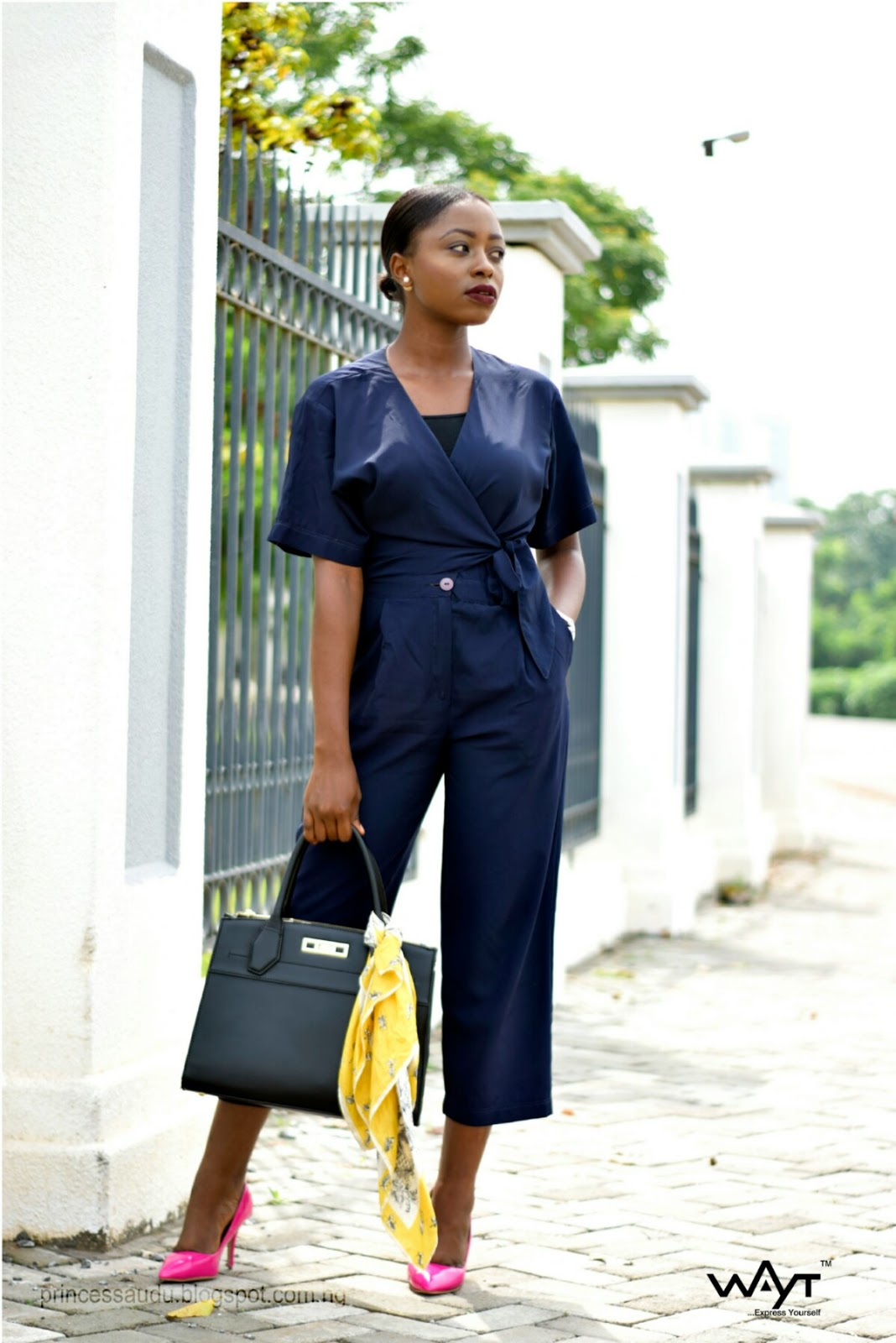 navy blue wrap jumpsuit, black statement back, pink court shoes