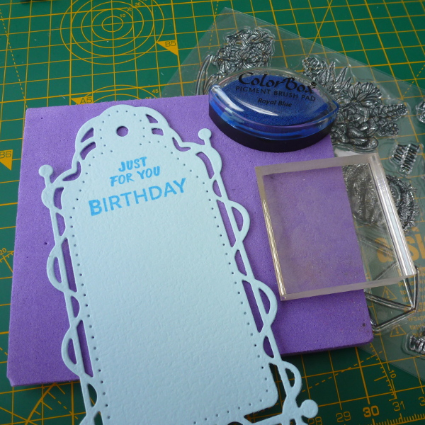 Inking a blue stamped sentiment onto the tonic studios tag birthday color box pigment brush pad royal blue