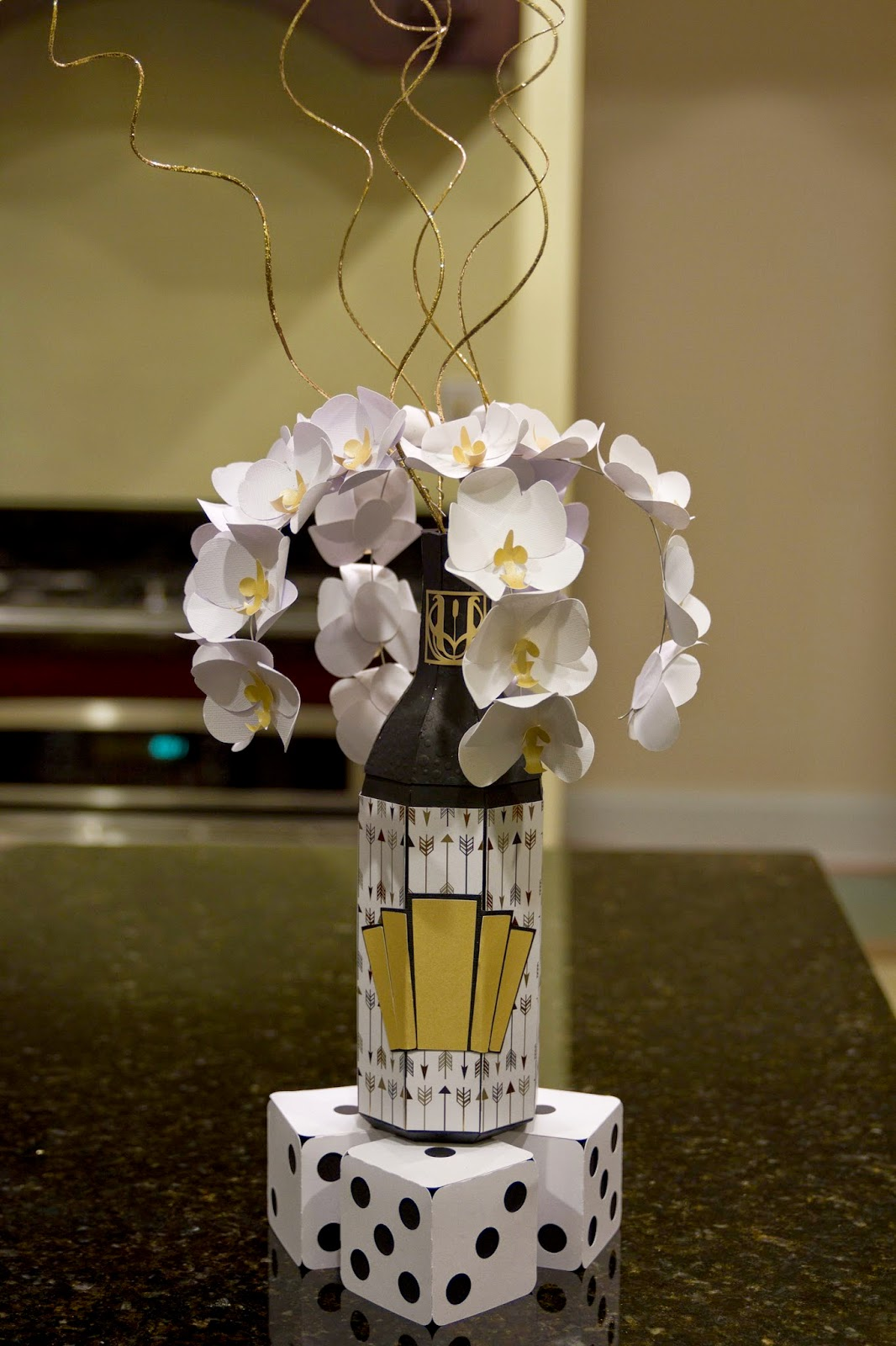 paper champagne bottle with orchids casading out of the top standing on top of large dice